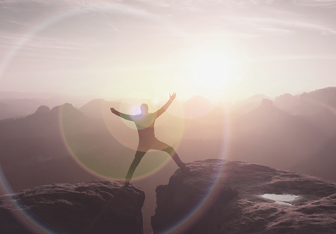 Jumping hiker celebrate triumph on cliff
